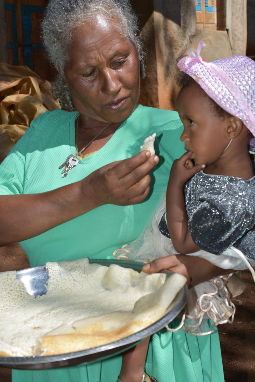 Sequare Regassa feeds her granddaughter with maize injera. (Photo: Simret Yasabu/CIMMYT)