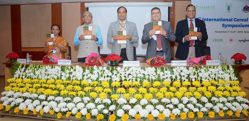 Organizers hold copies of the abstract book, released during the symposium.
