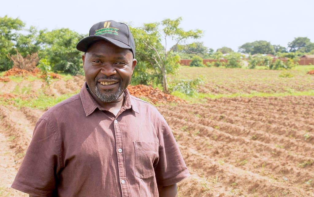 Chingati Phiri stands in front of a CPM plot reading for sowing in Bunda, Malawi. (Photo: Emma Orchardson/CIMMYT)