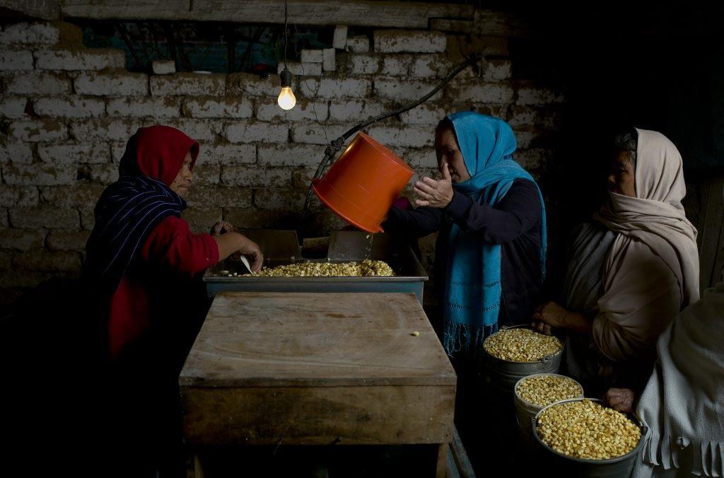 Women mill nixtamalized maize in Michoacan, Mexico. (Photo: Peter Lowe/CIMMYT)