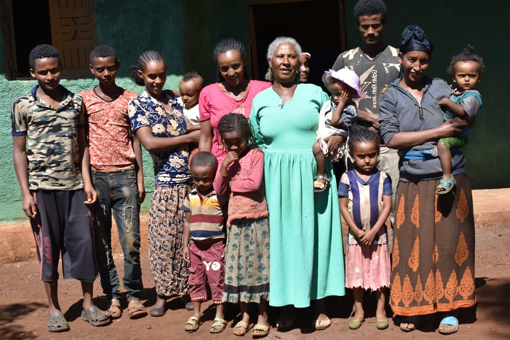 Sequare Regassa (wearing green) and her family stand for a group photo at their farm. (Photo: Simret Yasabu/CIMMYT)