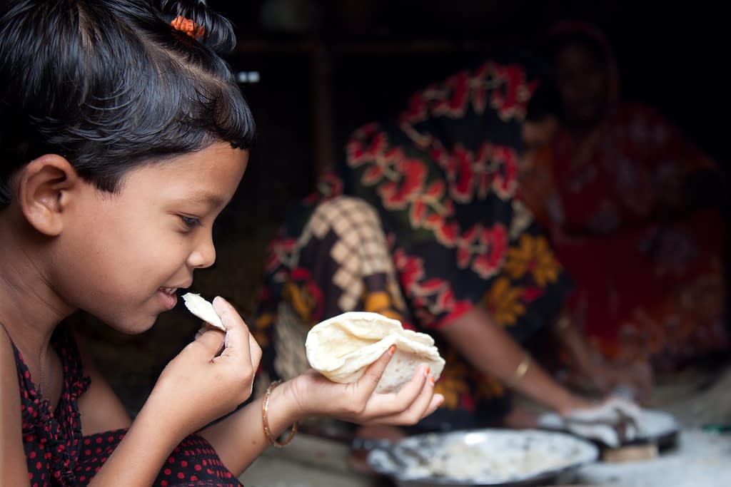 A little girl eats a freshly-made roti while the women of her family prepare more, at her home in the village of Chapor, in the district of Dinajpur, Bangladesh. (Photo: S. Mojumder/Drik/CIMMYT)