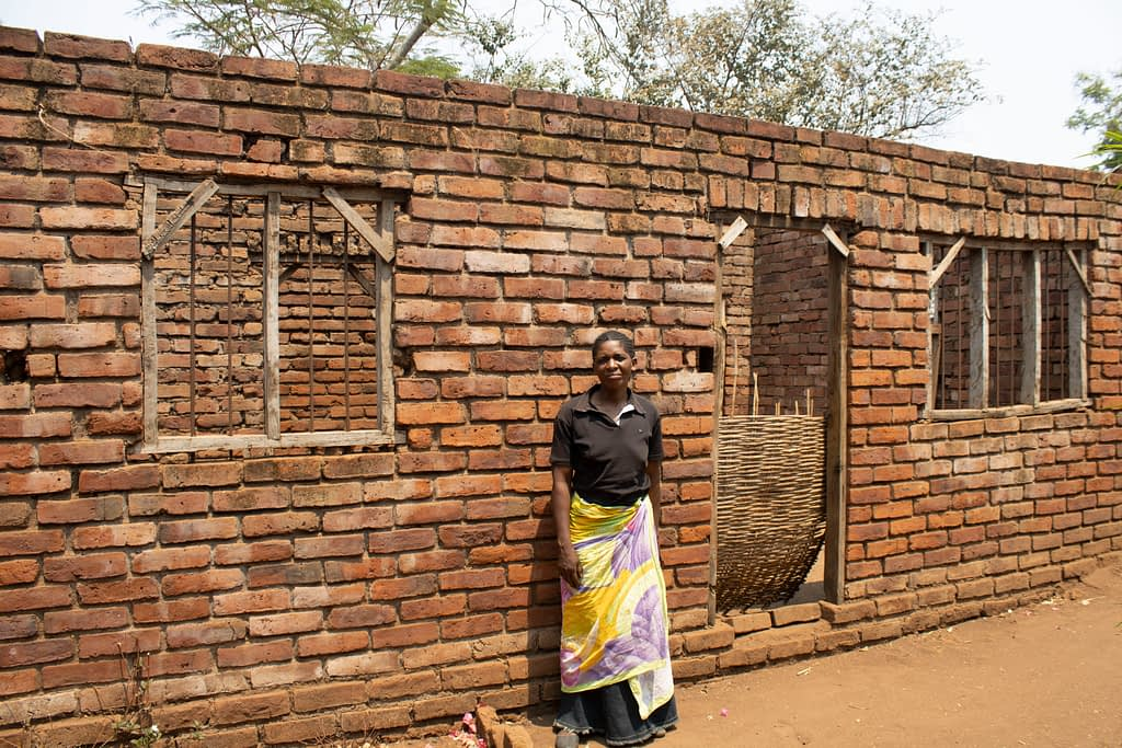 Through surplus sales of maize grain, pigeon pea and groundnuts over the past 12 years, Mary has generated enough income to build a new home. Nearing completion, she has purchased iron sheets for roofing this house by the end of 2019. (Photo: Shiela Chikulo/CIMMYT)