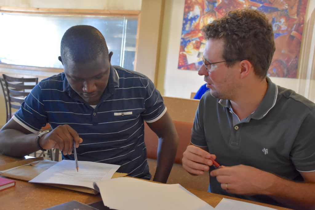 Pieter Rutsaert (right) discusses a research study questionnaire with consultant enumerator Victor Kitoto. (Photo: Jerome Bossuet/CIMMYT)