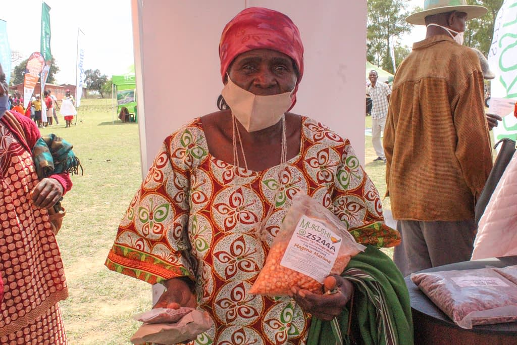A customer shows off her orange maize purchases at a seed fair in Masvingo, Zimbabwe. (Photo: S. Chikulo/CIMMYT)