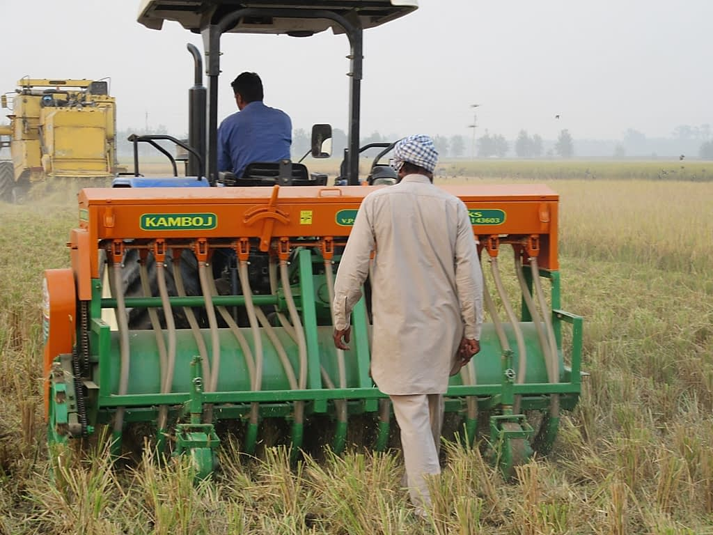 """Direct sowing of wheat seed into a recently-harvested rice field using the """"Happy Seeder"""" implement, a cost-effective and eco-friendly alternative to burning rice straw, in northern India. (Photo: BISA/Love Kumar Singh)"""