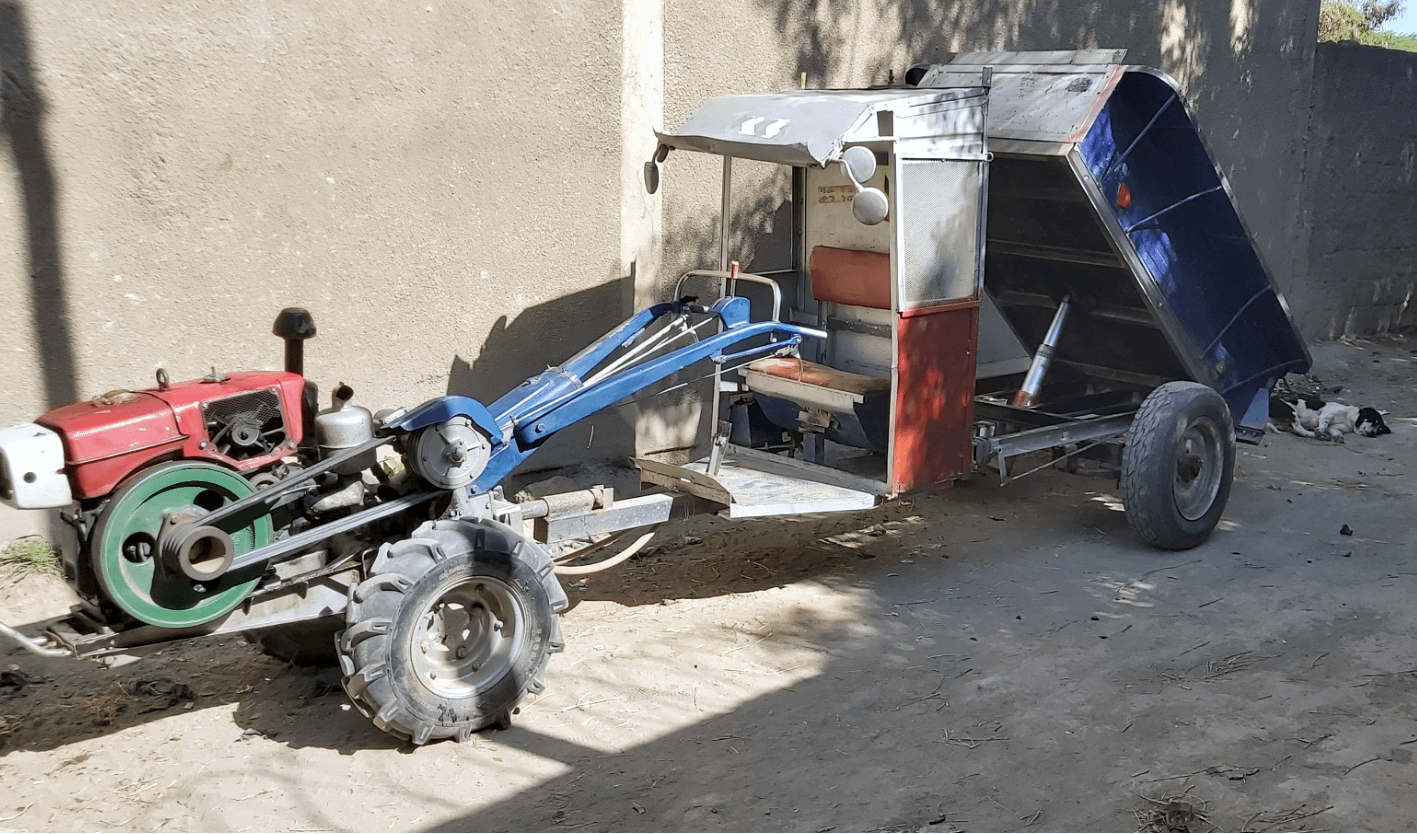 A two-wheel tractor with an improved driver seat and hydraulic tipping trailer system sits in from of Beyene Chufamo's workshop in Meki, Ethiopia. (Photo: CIMMYT)