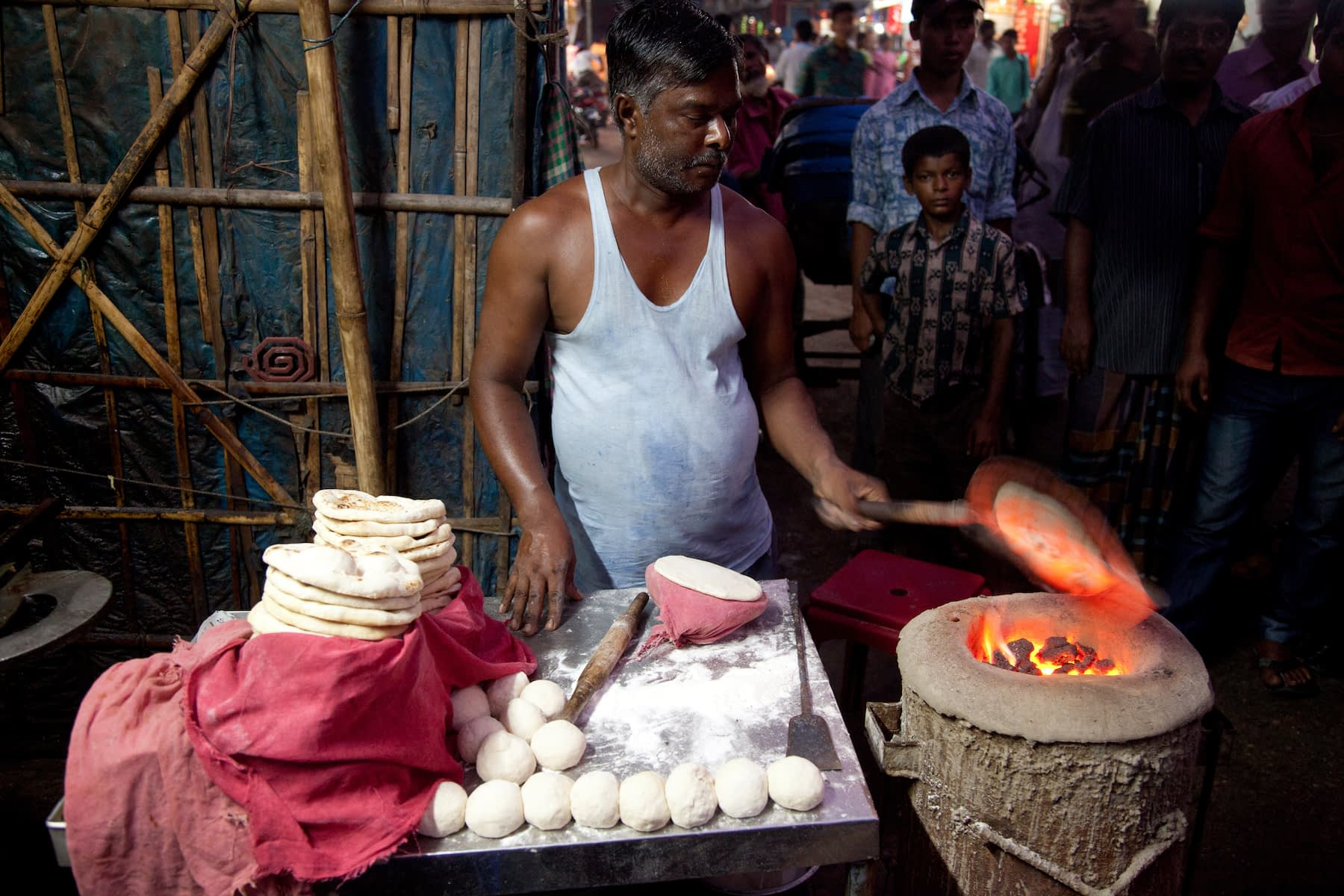 """A baker makes the traditional wheat flatbread known as """"naan roti"""" in Dinajpur, Bangladesh. (Photo: S. Mojumder/Drik/CIMMYT)"""