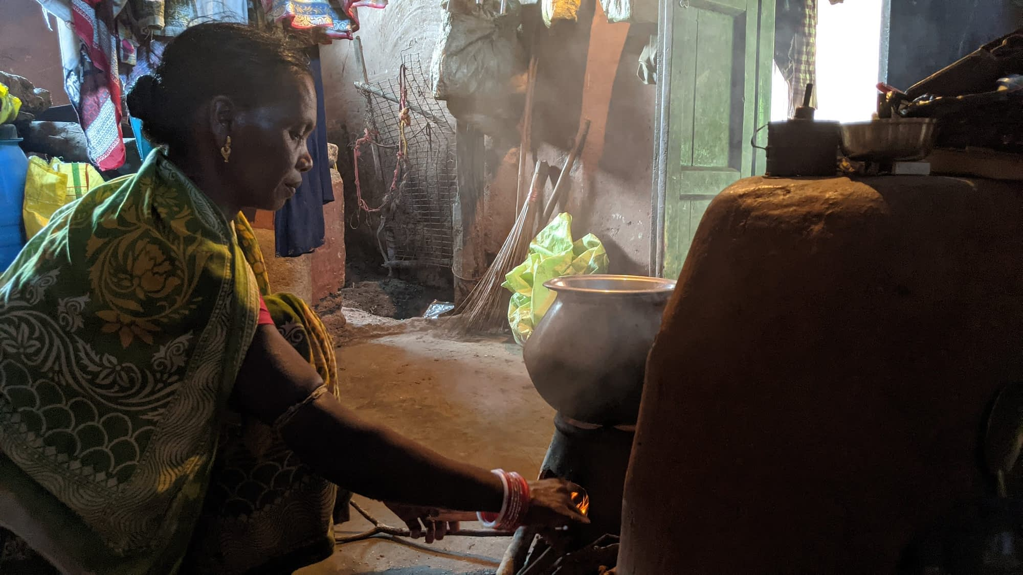 Anita Naik lights up her wood fire stove to prepare food, at her family home in the village of Badbil, in the Mayurbhanj district of India's Odisha state. (Photo: CIMMYT)