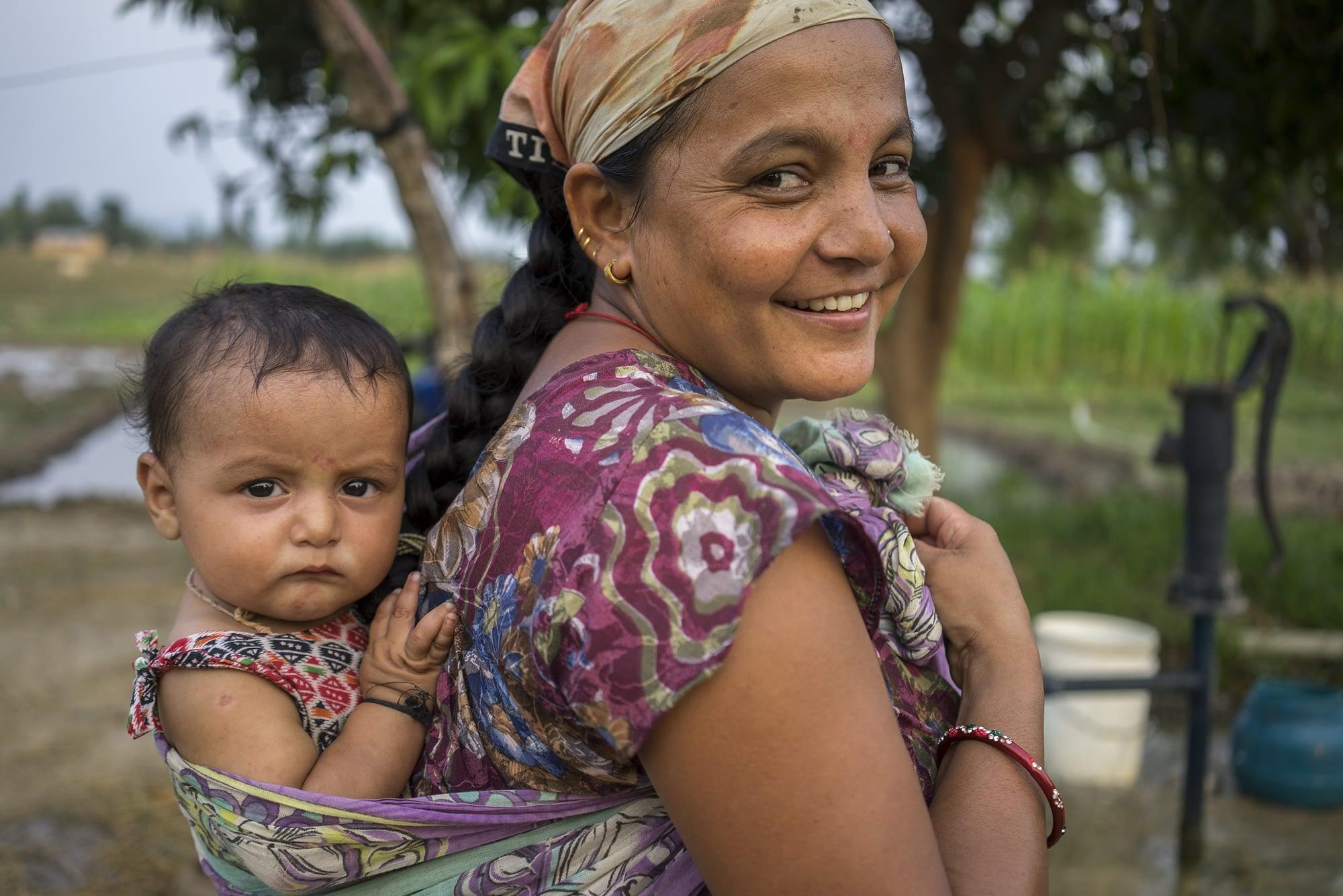Farmer Bhima Bhandari returns home after field work carrying her 7-month-old son Sudarsan on her back in Bardiya, Nepal. (Photo: Peter Lowe/CIMMYT)