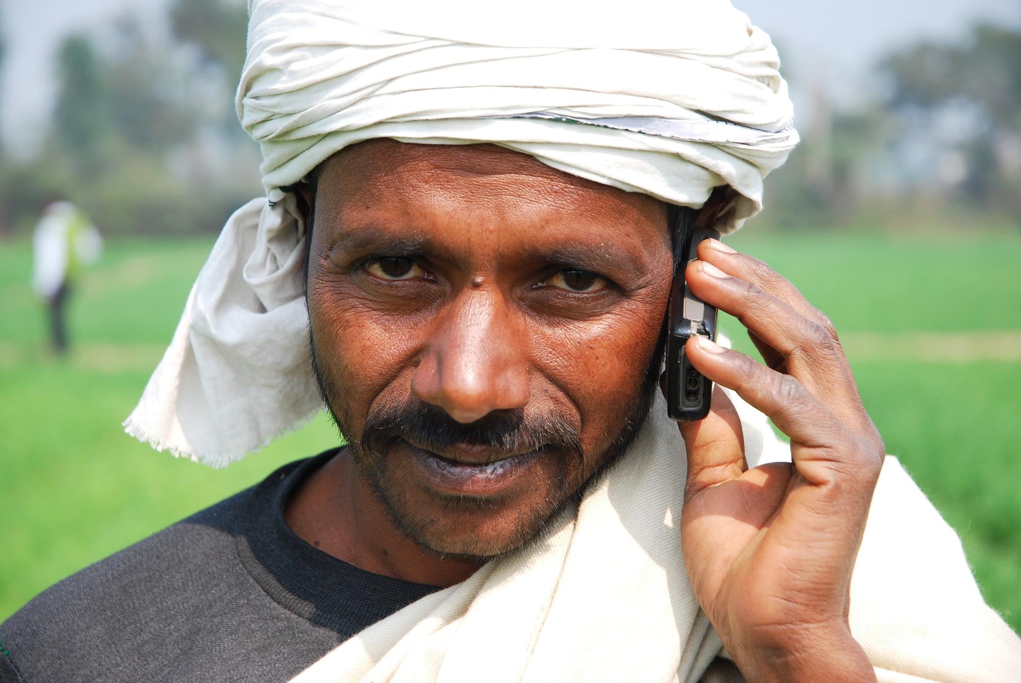 Farmer speaks on mobile phone in field.
