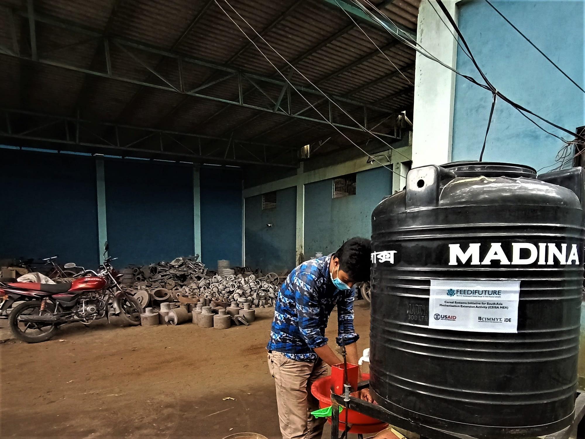 Man washes hands in workshop.