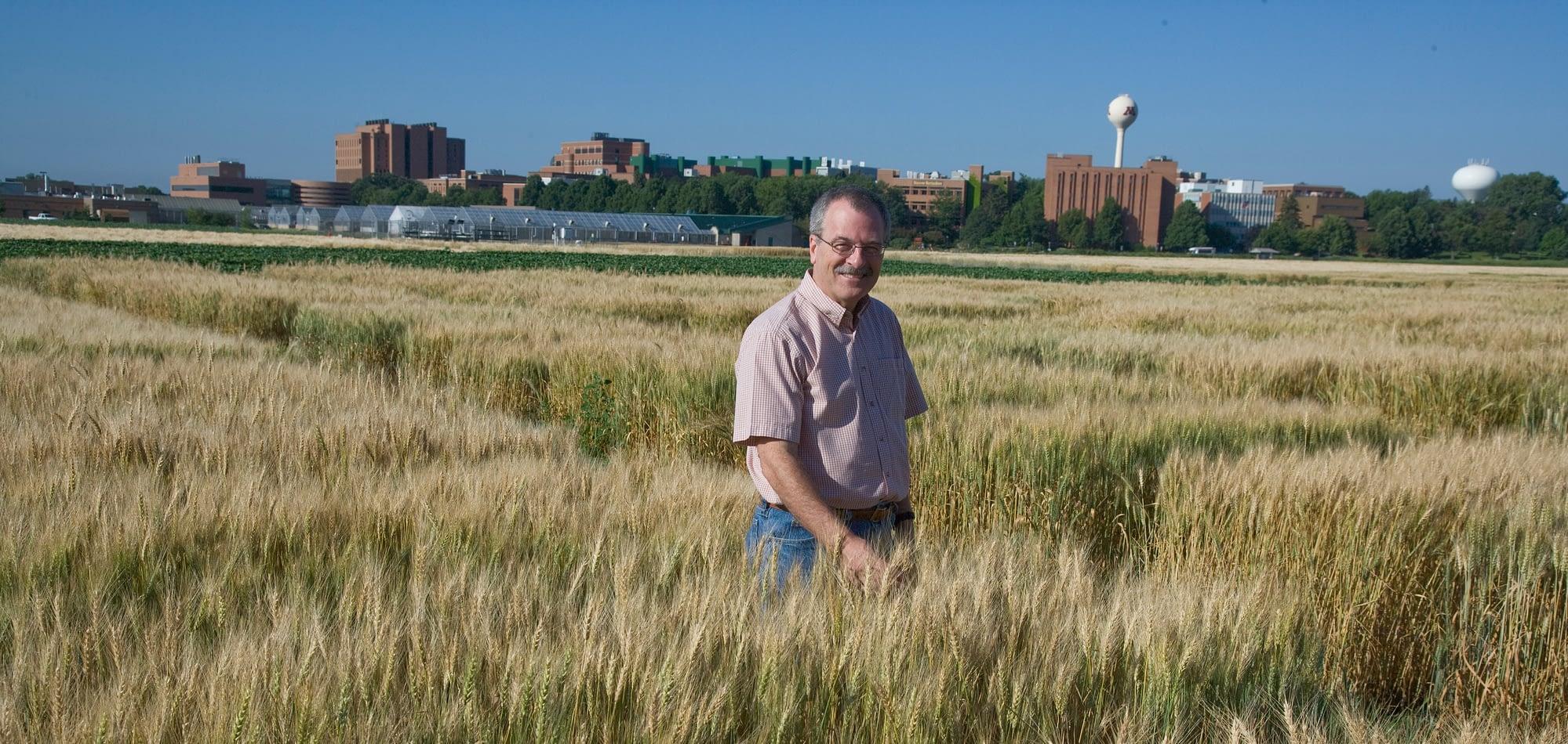 Philip Pardey stands in a wheat field. (Photo: David Hansen/University of Minnesota)