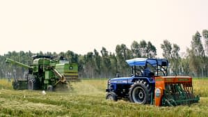 A combine harvester equipped with the Super SMS (left) harvests rice while a tractor equipped with the Happy Seeder is used for direct seeding of wheat. (Photo: Sonalika Tractors)