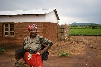 Belita Maleko, a farmer in rural Malawi, stands in front of her house. Photo: T. Samson/CIMMYT.