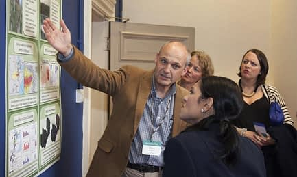 David Hodson, CIMMYT senior scientist (L), describes the challenges posed by wheat rust to Priti Patel, Britain's international development secretary, during the Grand Challenges Annual Meeting in London. Handout/DFID