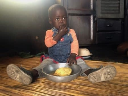 Ashley Muzhange, 18 months old, eats sadza porridge in the Chiweshe Communal Area. This porridge is made of vitamin A orange maize, a variety improving the nutrition of children and families in Zimbabwe.