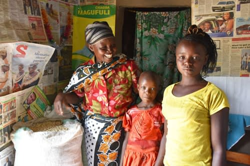 Valeria and her daughters and part of their bountiful maize harvest from 'ngamia' seed. B. Wawa/CIMMYT