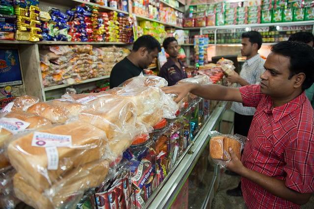 A customer chooses bread in a small shop in Dinajpur, Bangladesh. (Photo: S. Mojumder/Drik/CIMMYT)