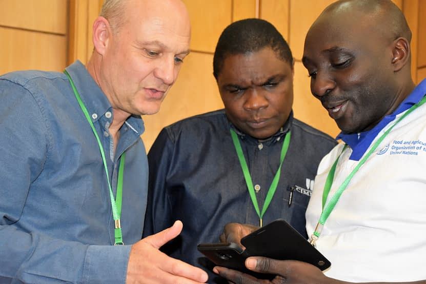 CIMMYT researchers Dave Hodson (left) and Francis Mwatuni (center) discuss MLN issues with another delegate during the 3-year MLN project review workshop. (Photo: Joshua Masinde/CIMMYT)