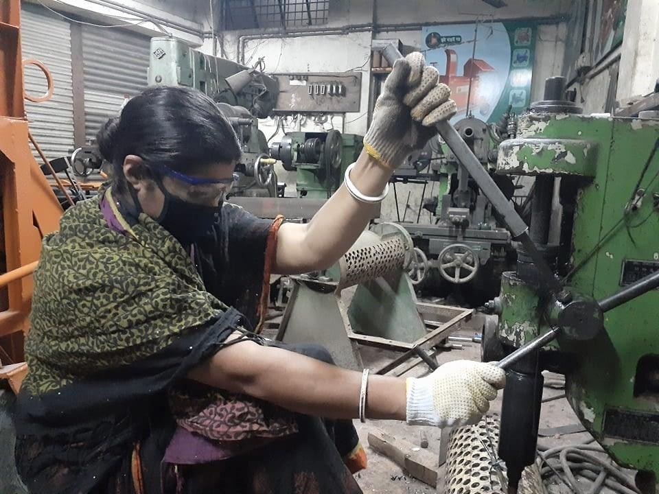 Woman works machinery.